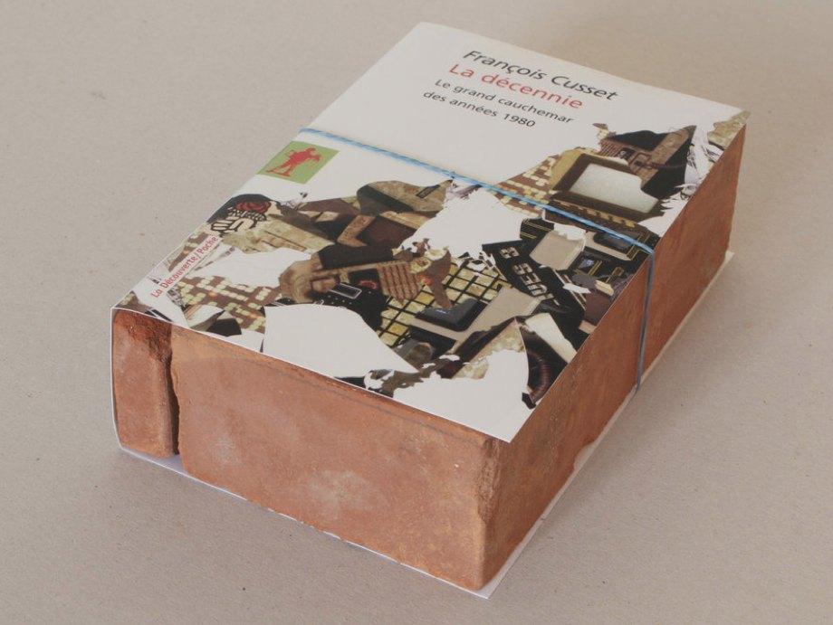 Claire Fontaine La décennie brickbat, 2009 Brickfragments and digital archival print with optional elastic band, 18.9 × 12.5 × 5.6 cm