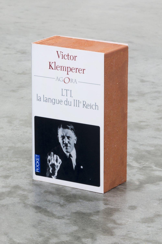 Claire Fontaine LTI, la langue du IIIème Reich brickbat, 2014 Brickfragments and digital archival print with optional elastic band, 17.8 × 10.8 × 5.8 cm