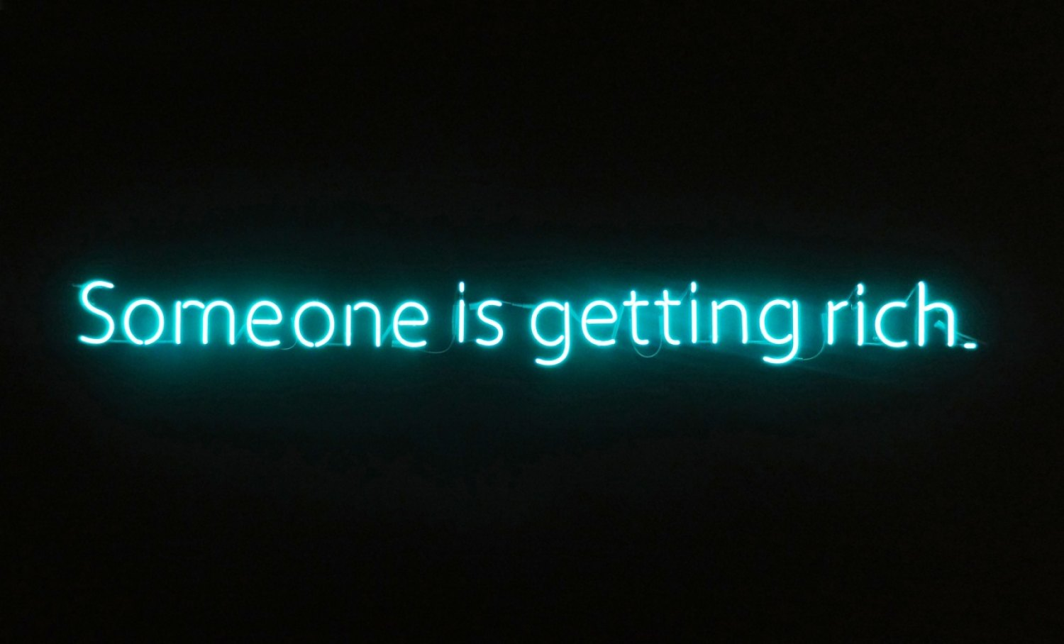 Claire Fontaine  Untitled (Someone is getting rich), 2012 Tecnolux No.9 Super Turquoise, 10mm glass, mounted to black painted wall, window or ceiling, 15 × 223 × 4 cm
